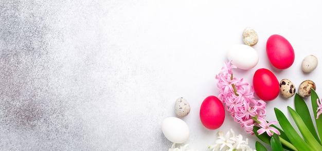 Composizione primaverile. uova di pasqua, giacinto rosa e rosa su fondo di pietra. banner orizzontale. copia spazio per testo - immagine