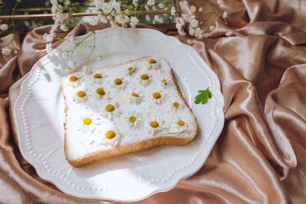 Composizione primaverile, sandwich di pane tostato con fiori di camomilla