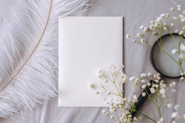 Composizione primaverile, carta bianca vuota bianca, fiori di gypsophila, lente d'ingrandimento e piuma bianca