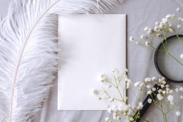 Composizione di primavera, carta bianca vuota bianca, fiori di gypsophila, lente d'ingrandimento