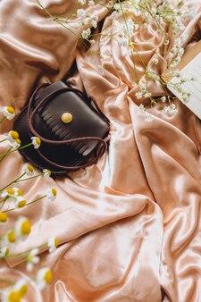 Composizione primavera, fiori di gipsofila bianchi, camomilla e portamonete in pelle su tessuto satinato dorato