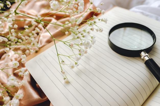 Composizione primavera, fiori di gipsofila bianca con taccuino e lente d'ingrandimento su tessuto satinato oro