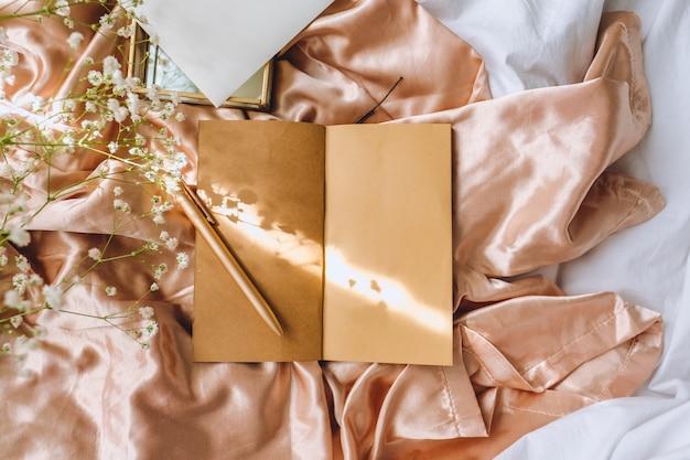 Composizione primavera, fiori di gipsofila bianchi con taccuino e penna su tessuto satinato oro