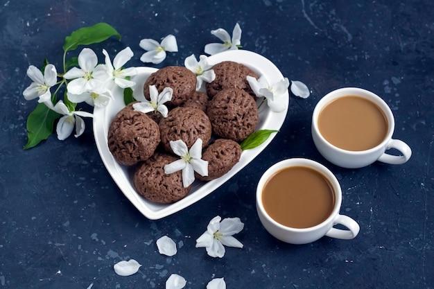 Composizione di primavera con fiori di melo e biscotti al cioccolato fatti in casa