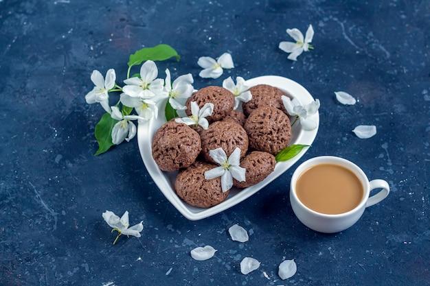Composizione di primavera con fiori di melo e biscotti al cioccolato fatti in casa.