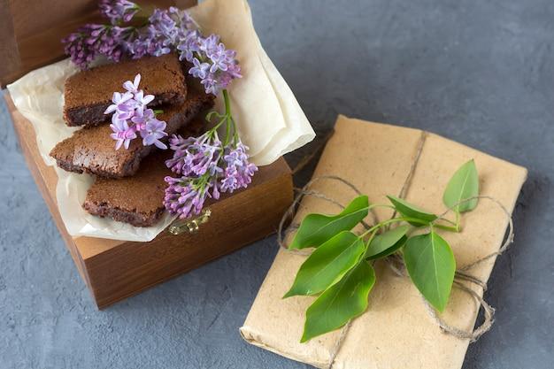 Composizione di primavera con confezione regalo, fiori lilla e brownie, torta bagnata. dessert da servire per la pausa tè o caffè in scatola di legno. fai uno spuntino in una giornata di primavera in giardino.