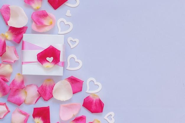 Composizione primaverile con petali e cuori su uno sfondo pastello