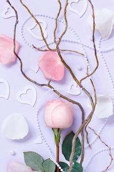 Composizione di primavera con rose, petali e cuori su uno sfondo pastello