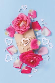 Composizione primaverile con rose, petali, cuori e confezione regalo su uno sfondo pastello