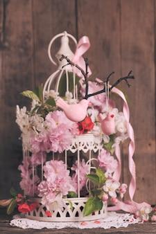 Decoro primaverile - uccelli rosa sul ramo in gabbia shabby chic con fiori