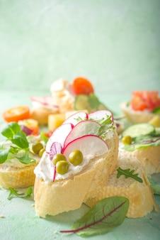 Priorità bassa dell'alimento sano di dieta di primavera. panino per la colazione con pane tostato baguette con crema di formaggio, varie verdure fresche