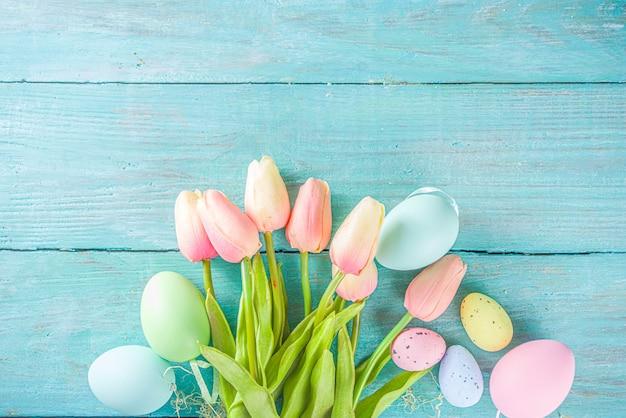 Fondo di festa di pasqua e di primavera con i fiori del tulipano, uova pastello colorate sulla vista superiore del tavolo blu. auguri di buona pasqua.
