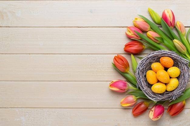 Tulipani di pasqua della primavera nel secchio sull'annata bianca