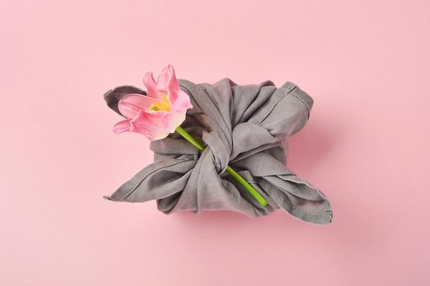 Regalo ecologico primaverile avvolto in tessuto grigio con un fiore di tulipano rosa