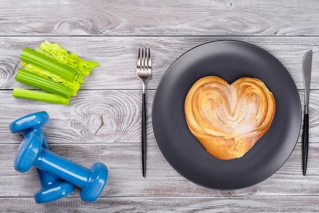 Composizione sportiva flatlay primavera con sedano e manubri blu e piatto con panetteria su sfondo di legno. concetto di stile di vita sano o fast food, sport e dieta in primavera. vista dall'alto.