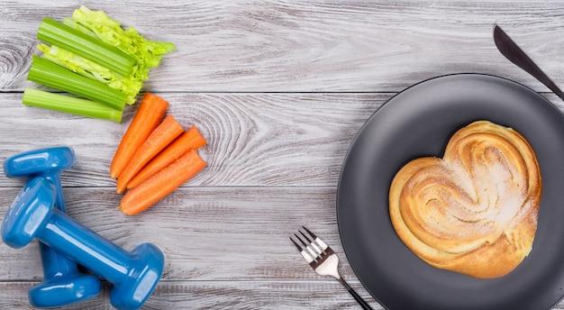 Composizione sportiva flatlay primaverile con sedano e carote blu manubri e piatto con panetteria su sfondo di legno. concetto di stile di vita sano o fast food, sport e dieta in primavera. vista dall'alto.