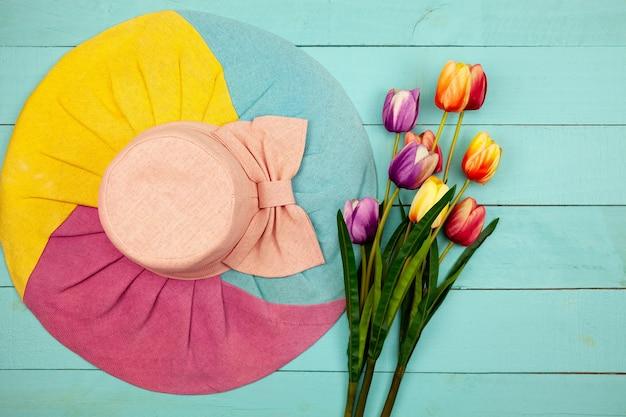 Fiore di primavera di tulipani multi colore e cappello estivo donna su spazio copia legno spazio per il testo.