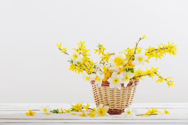 Merce nel carrello dei fiori della primavera su fondo bianco