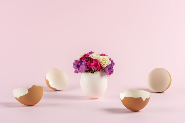 Fiori primaverili in guscio d'uovo rotto con uova di pasqua rotte su sfondo rosa pastello