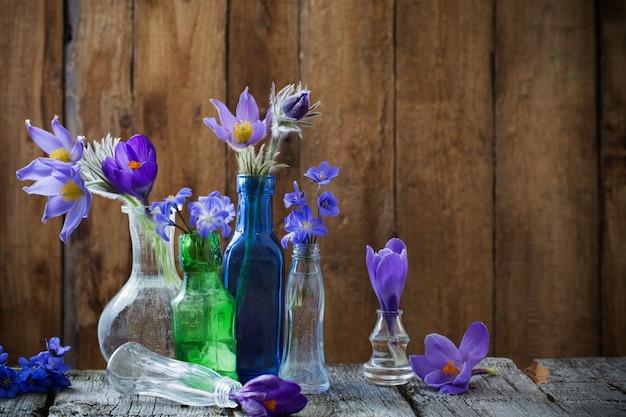 La primavera fiorisce in navi di vetro su una tavola di legno