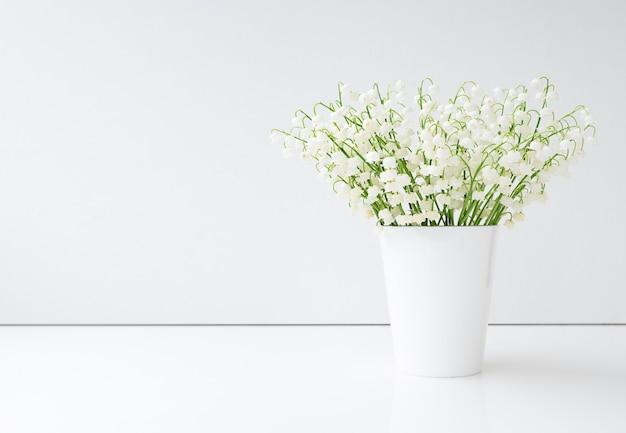 Fiori di primavera mughetto in vaso bianco. copia spazio. minimalismo