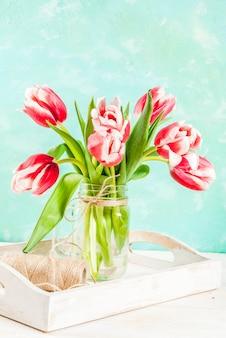 Primavera . fiorisce i tulipani in un barattolo di vetro, su un bianco azzurro e di legno.