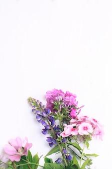 Fiori primaverili su uno sfondo di legno bianco
