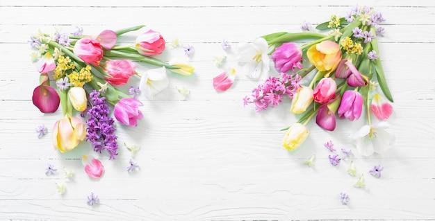Fiori di primavera su una superficie di legno bianca