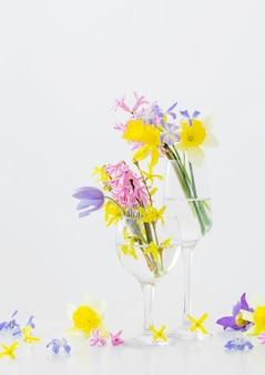 Fiori di primavera in bicchiere di vino sulla superficie bianca