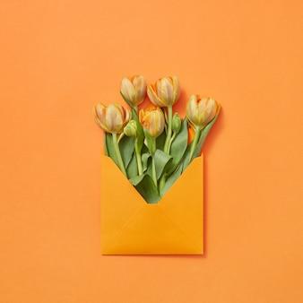Tulipani di fiori freschi di primavera in busta artigianale su uno sfondo giallo con spazio di copia. lettera d'amore per le congratulazioni. lay piatto
