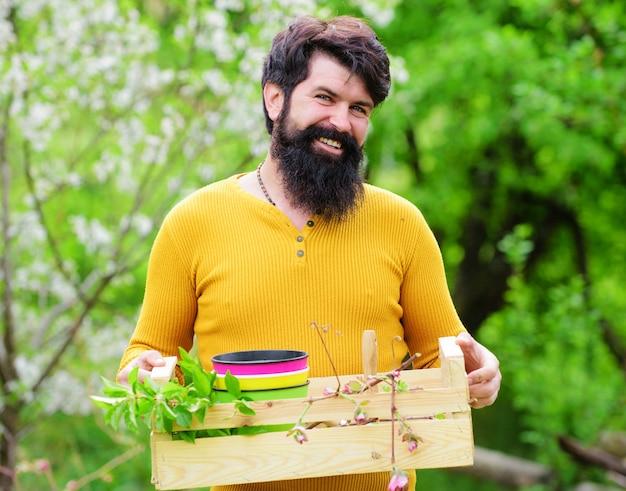 Giardinaggio primaverile, uomo sorridente che si prepara per la semina, lavoro in giardino, lavoro di giardiniere.