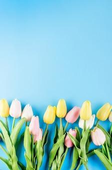 Concetto di primavera o vacanza, un bouquet di tulipani su sfondo blu.