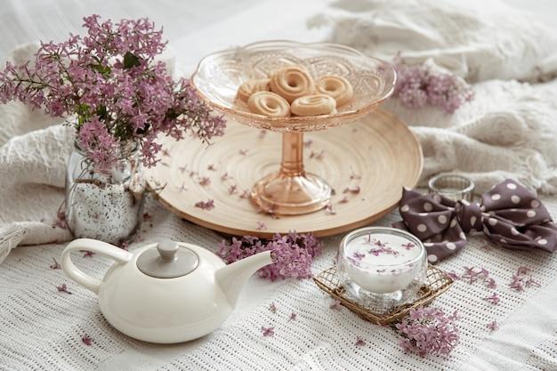 Natura morta in casa primaverile con fiori lilla, dolci, latte e dettagli decorativi decor