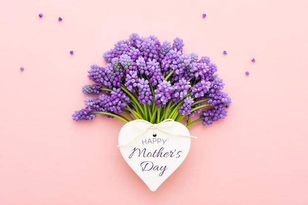 Fiori di primavera lilla e una carta a forma di cuore con testo happy mother's day su sfondo rosa. lay piatto.