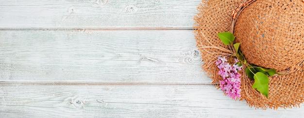 Fiori di primavera lilla e un cappello di paglia su un fondo di legno bianco