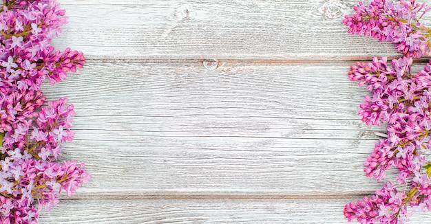 I fiori primaverili lilla e un cappello di paglia su un tavolo di legno bianco sono un posto libero per inserire il testo. minimalismo, design, vista dall'alto. flatlay
