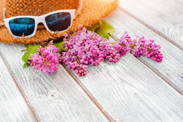Fiori di primavera lilla e un cappello di paglia su un tavolo di legno bianco