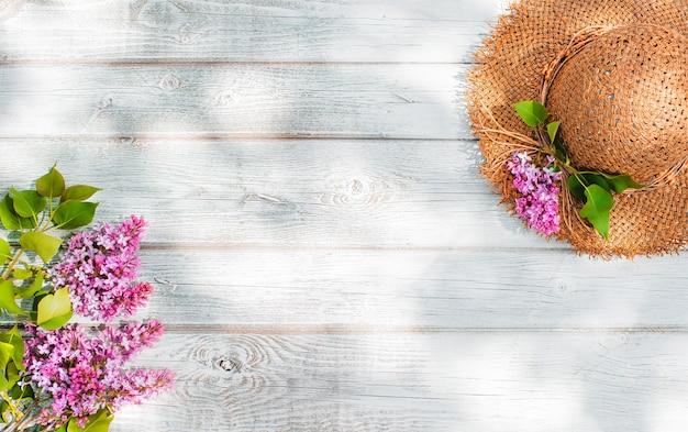 I fiori primaverili lilla e un cappello di paglia su una parete di legno bianca sono un posto libero per inserire il testo. minimalismo, design, vista dall'alto. flatley