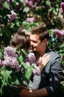 Primavera amore incontri romanticismo felice coppia di innamorati che si baciano e si abbracciano su sfondo lilla sfocato