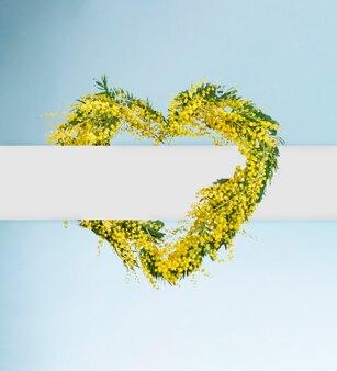 Ghirlanda di fiori di mimosa primaverile a forma di cuore con spazio di copia. festa della donna, festa della mamma, concetto di carta di primavera