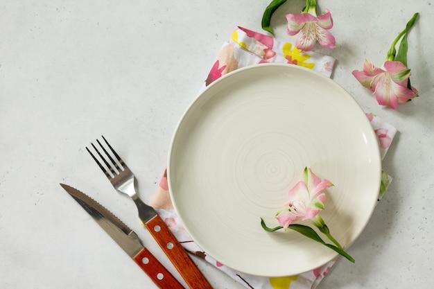 Tavola primaverile o per la festa della mamma posate e tovaglioli su un tavolo di pietra bianca