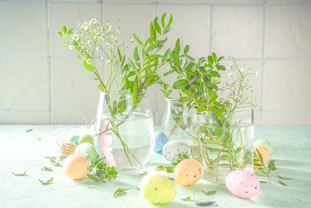 Concetto di rinascita della natura primaverile. piante verdi e fiori selvatici da giardino in diversi bicchieri e vasi su uno sfondo verde, interni di casa