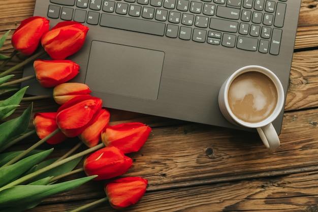 Concetto di ufficio primavera sullo sfondo di legno con laptop e tazza di caffè bianca su di esso. alcuni tulipani rossi.