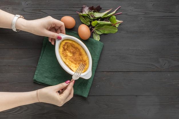Frittata di primavera con verde per il bambino in una padella sulla superficie in legno rustico Foto Premium