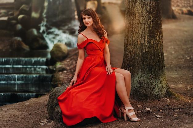Primavera ritratto di una ragazza che ride in un lungo abito rosso con i capelli lunghi, passeggiate nel parco nel bosco