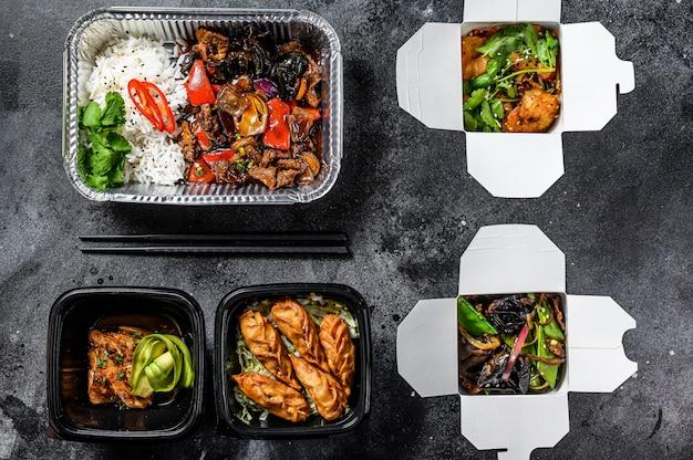 Involtini primavera, gnocchi, gyoza e wok in scatola da asporto. pranzo salutare prendi e vai alimenti biologici. sfondo bianco. vista dall'alto
