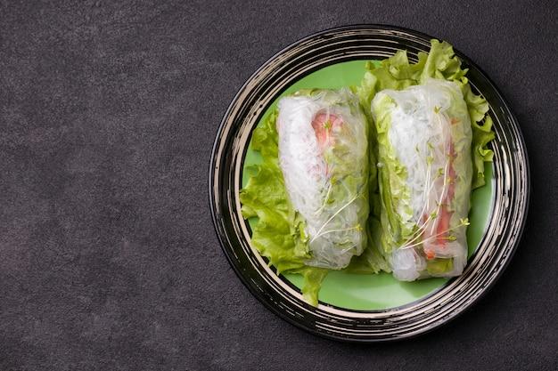 Involtini primavera sul piatto verde accanto a una salsa grigia su fondo nero.