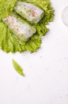 Involtini primavera di verdure su foglie verdi su bianco. vicino alle tagliatelle con spazio di copia. piatto vegetariano