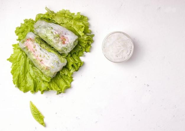 Involtini primavera di verdure su foglie verdi su bianco. posto per il testo