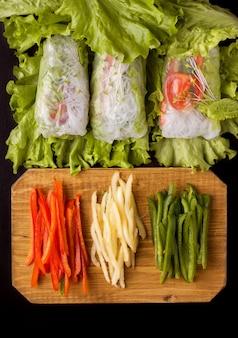 Involtini primavera con verdure su fondo nero. vicino agli ingredienti del pepe tritato